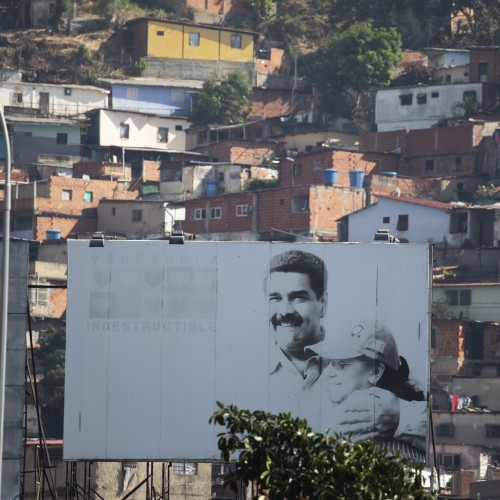 A billboard, backdropped by the Catia neighborhood, promotes an image of Venezuelan President Nicolas Maduro